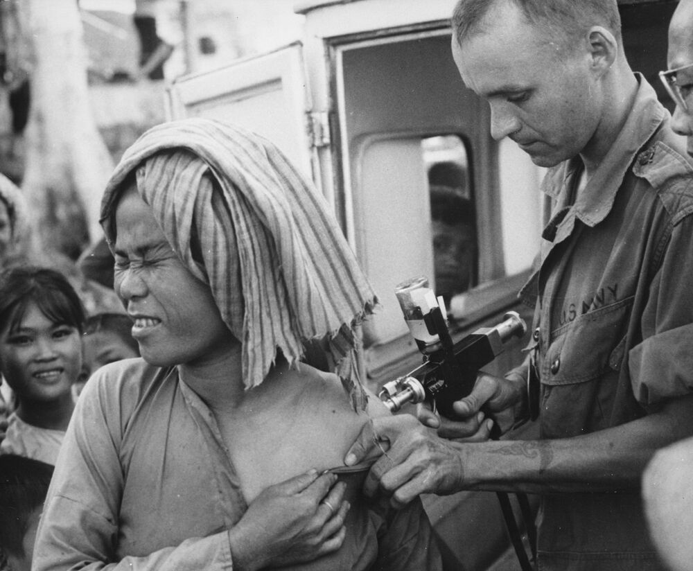 A U.S. Navy hospital corpsman, member of a USAID military health team, inoculates a flood refugee against cholera at the refugee centre on Nui Sam mountain, Chau Doc province., 1966