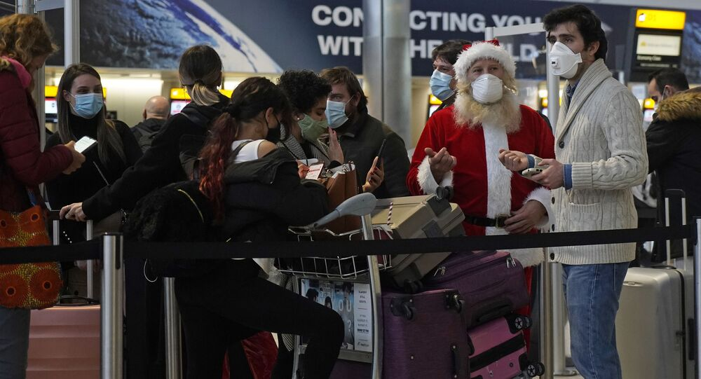 Travellers, one dressed in a Father Christmas outfit and all wearing face coverings, queue with their luggage in the departures hall at Terminal 2 of Heathrow Airport in west London on December 21, 2020, as a string of countries around the world banned travellers arriving from the UK, due to the rapid spread of a new, more-infectious coronavirus strain.