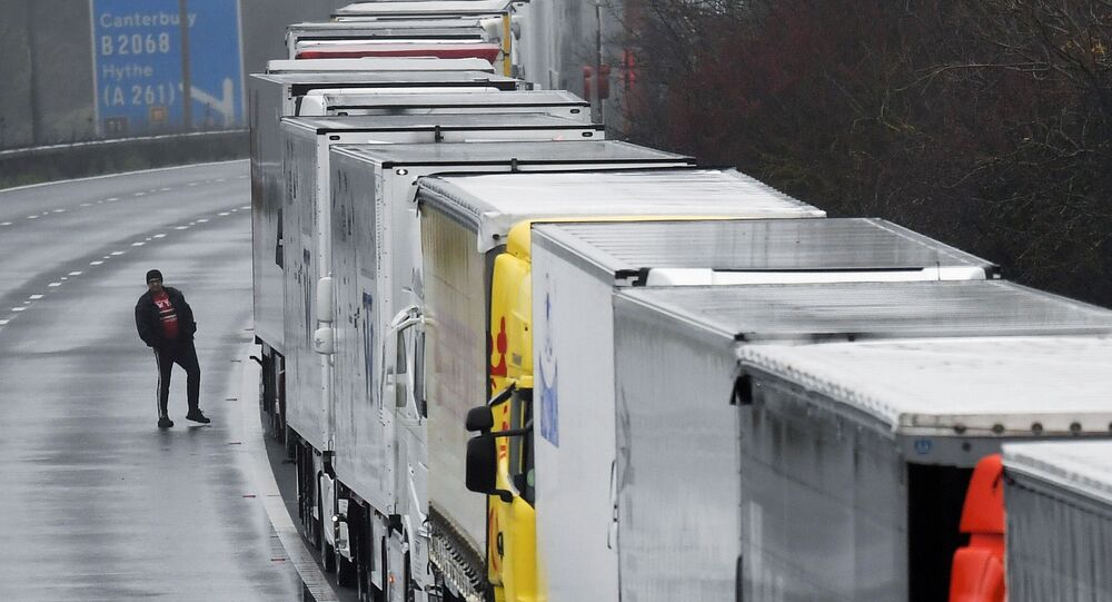 A driver walks next to lorries parked on the M20 motorway towards Eurotunnel and the Port of Dover, as EU countries impose a travel ban from the UK following the coronavirus disease (COVID-19) outbreak, in Folkestone, Britain, December 21, 2020. REUTERS/Toby Melville