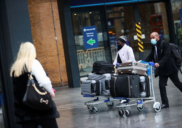 Travellers walk with their luggage at King's Cross station, as EU countries impose a travel ban from the UK following the coronavirus disease (COVID-19) outbreak, in London, Britain, December 21, 2020.