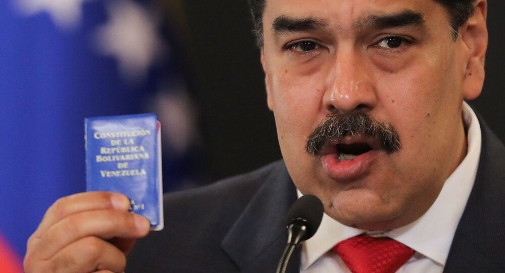 Venezuelan President Nicolas Maduro holds Venezuela's constitution as he speaks during a press conference following the ruling Socialist Party's victory in legislative elections that were boycotted by the opposition in Caracas, Venezuela December 8, 2020.