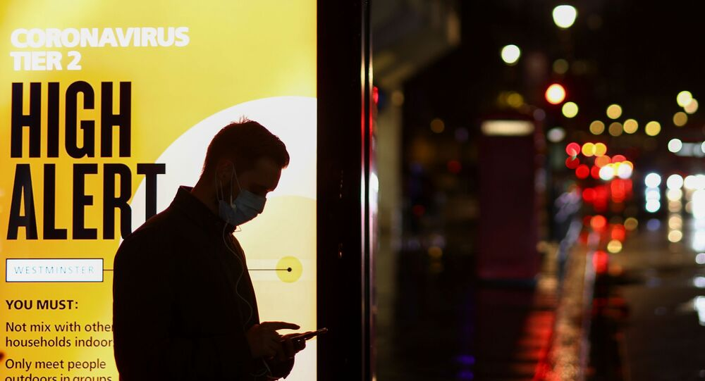 A man wearing a protective mask uses a phone at a bus stop, amidst the spread of the coronavirus disease (COVID-19), in London, Britain December 3, 2020