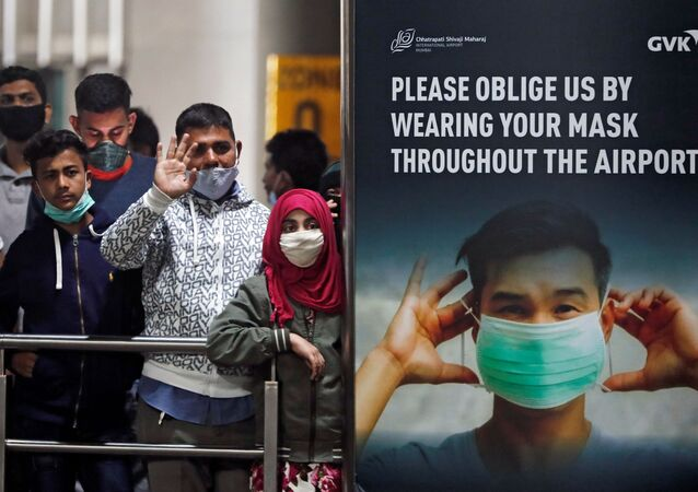 People wearing protective face masks wait for passengers to arrive at Chhatrapati Shivaji Maharaj International Airport after India cancelled all flights from the UK over fears of a new strain of the coronavirus disease (COVID-19), in Mumbai, India, December 22, 2020.