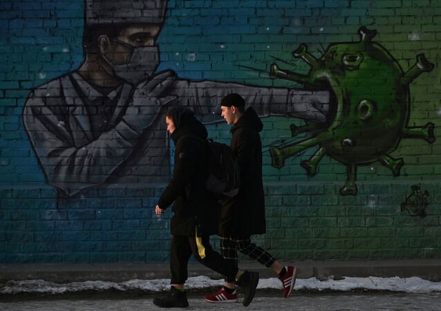 People walk past a graffiti depicting a healthcare worker fighting the virus, amid the outbreak of the coronavirus disease (COVID-19) in Omsk, Russia November 23, 2020