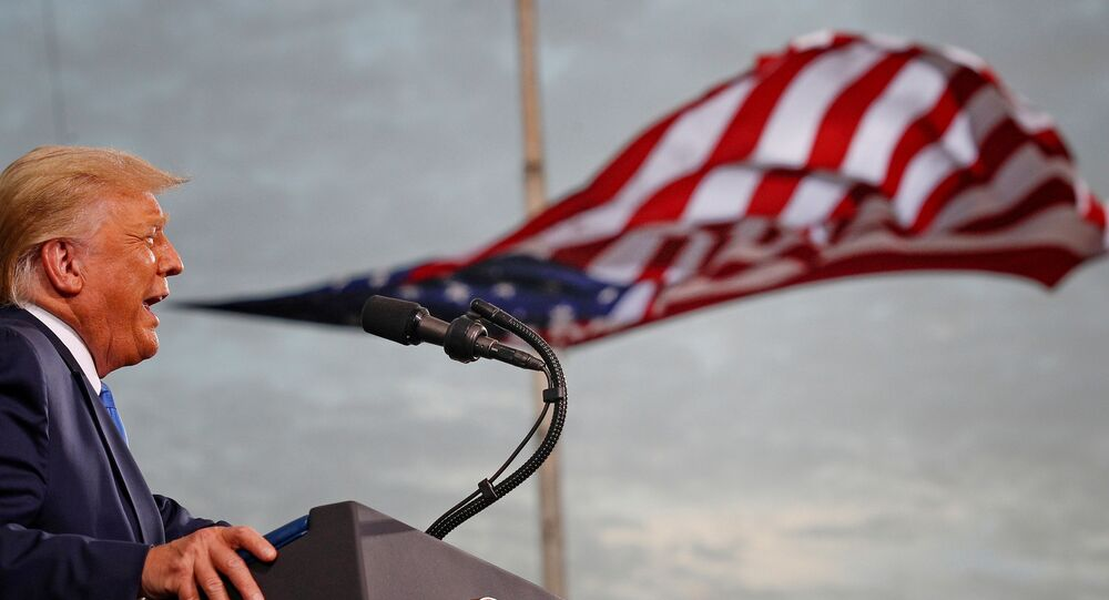 President Donald Trump speaks, with a flag behind him, during a campaign rally at Cecil Airport in Jacksonville, Florida, U.S., September 24, 2020