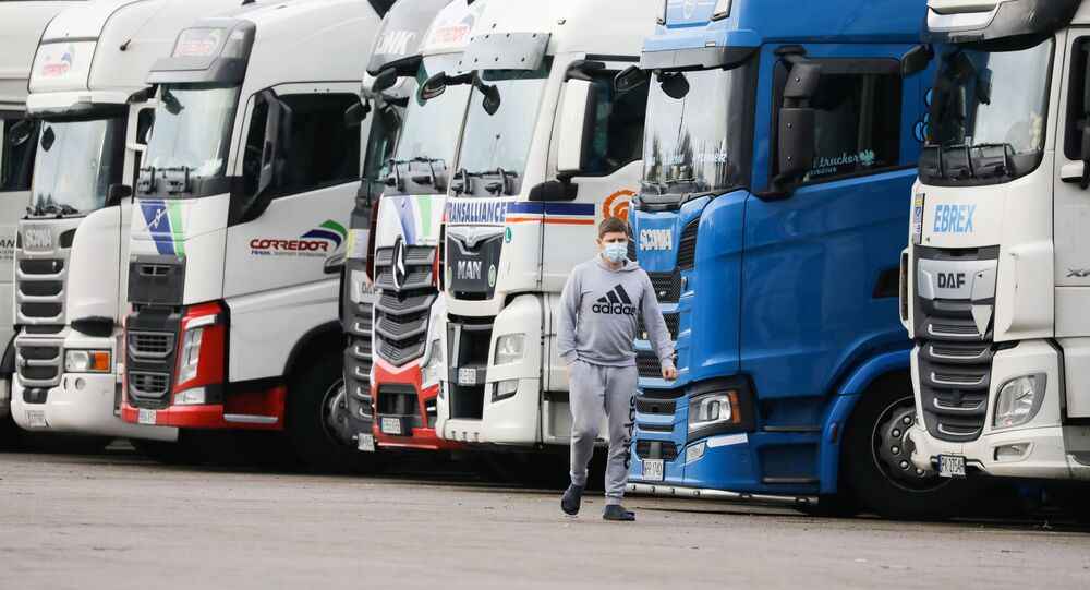 A driver wearing a face mask walks past lorries at Ashford International Truck Stop, as EU countries impose a travel ban from the UK following the coronavirus disease (COVID-19) outbreak, in Ashford, Britain December 22, 2020.