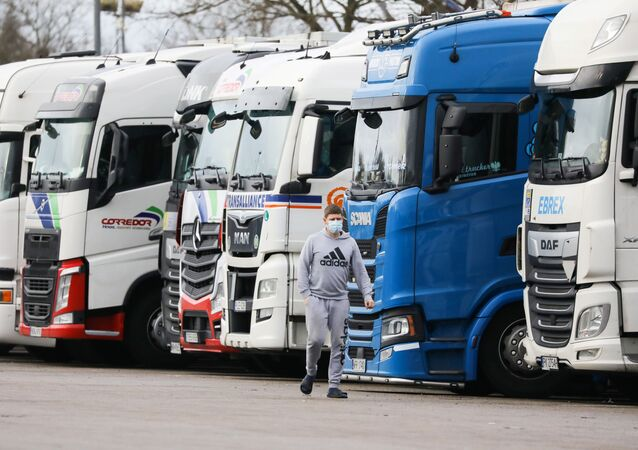 A driver wearing a face mask walks past lorries at Ashford International Truck Stop, as EU countries impose a travel ban from the UK following the coronavirus disease (COVID-19) outbreak, in Ashford, Britain 22 December 2020.