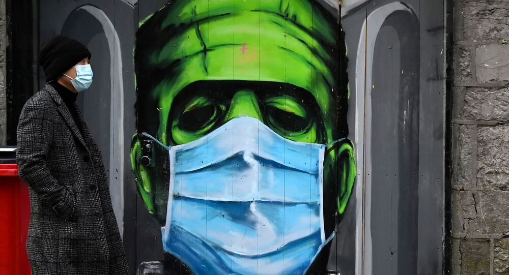 A man walks past a graffiti of a Frankenstein wearing a protective face mask on a doorway amid the spread of the coronavirus disease (COVID-19) pandemic, in Galway, Ireland, December 22, 2020