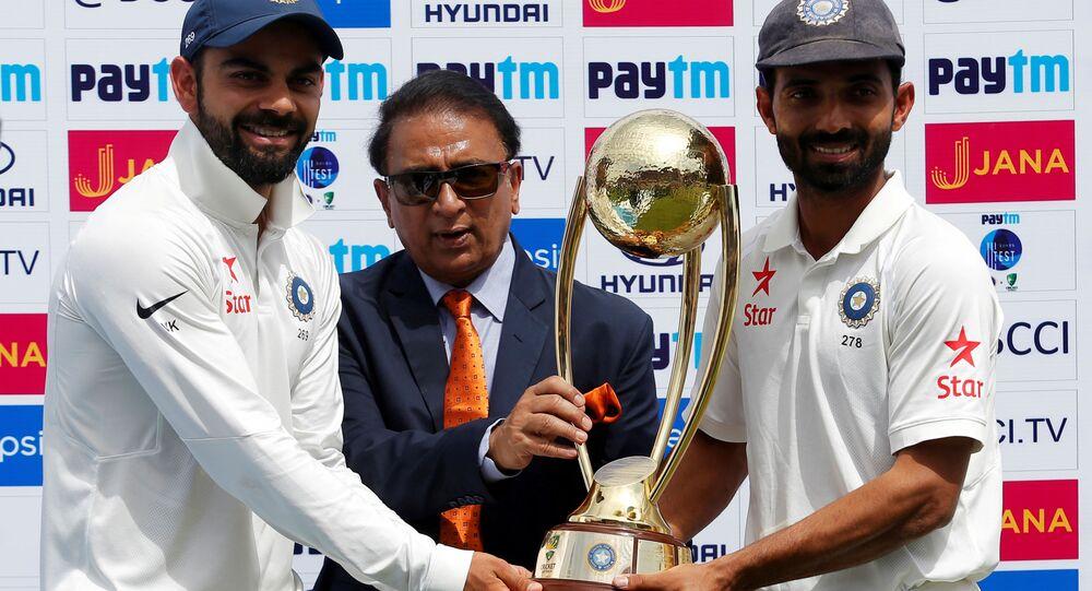 Cricket - India v Australia - Fourth Test cricket match - Himachal Pradesh Cricket Association Stadium, Dharamsala, India - 28/03/17 - India's Virat Kohli (L) and Ajinkya Rahane (R) receive the trophy from the former Indian cricket player Sunil Gavaskar after winning the series
