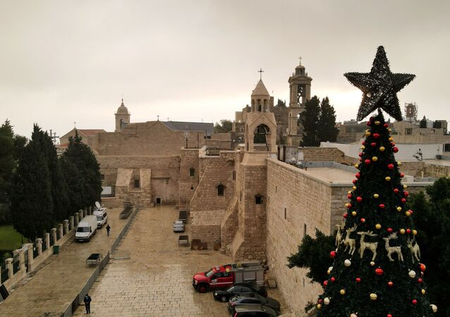 A picture taken with a drone shows the Church of the Nativity and a Christmas tree at Manger Square on Christmas Eve, in Bethlehem in the Israeli-occupied West Bank 24 December, 2020.