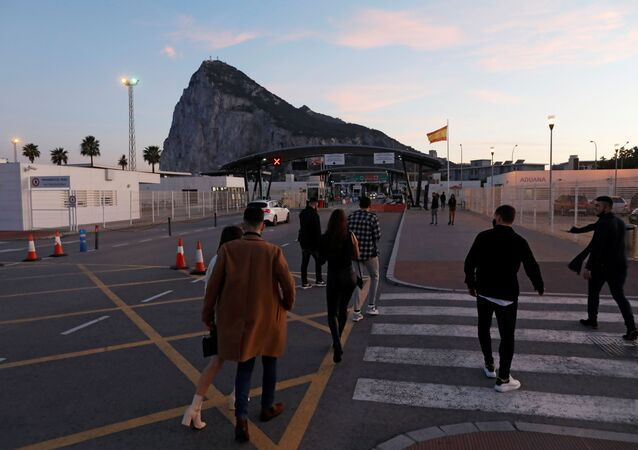 Gibraltarian citizens cross the country's border from Spanish side after spending the Christmas Eve day in Spain, in front of the Rock of the British overseas territory of Gibraltar, historically claimed by Spain, after Britain and the European Union agreed terms of a trade deal on Brexit on Thursday, in La Linea de la Concepcion, southern Spain, December 24, 2020.