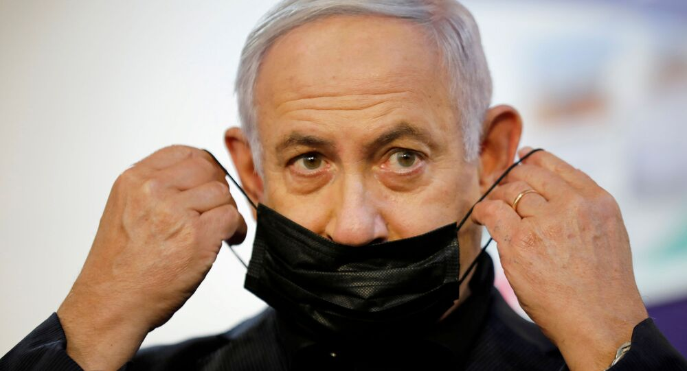 Israeli Prime Minister Benjamin Netanyahu adjusts his protective face mask after receiving a coronavirus disease (COVID-19) vaccine at Sheba Medical Center in Ramat Gan, Israel December 19, 2020.