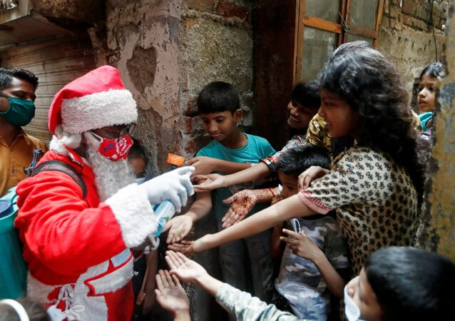 A man wearing a Santa Claus costume sanitizes children's hands inside a slum, amidst the spread of the coronavirus disease (COVID-19), in Mumbai, India, December 19, 2020