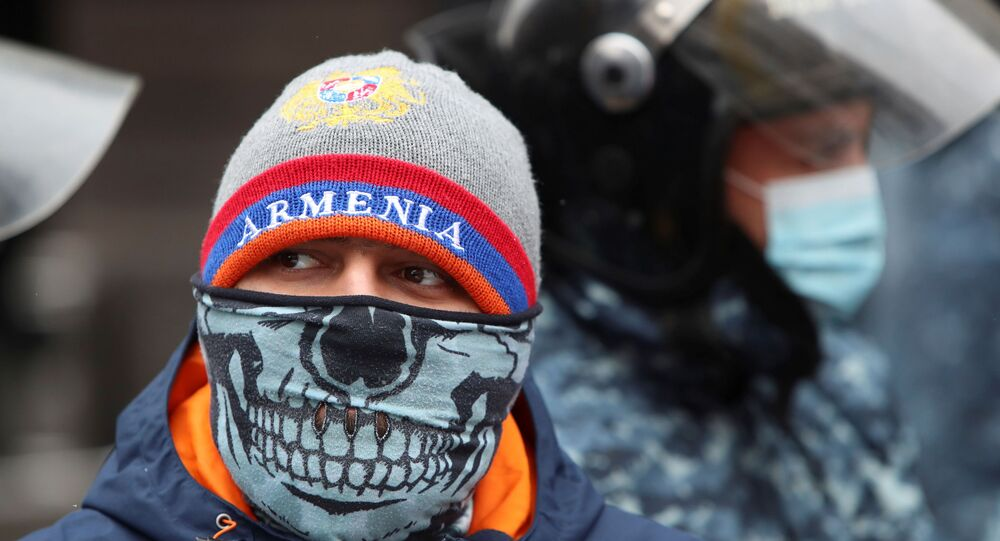 A participant wearing a face mask stands next to Armenian law enforcement officers outside the government office during an opposition rally to demand the resignation of Prime Minister Nikol Pashinyan following the signing of a deal to end a military conflict over Nagorno-Karabakh in Yerevan, Armenia December 24, 2020.