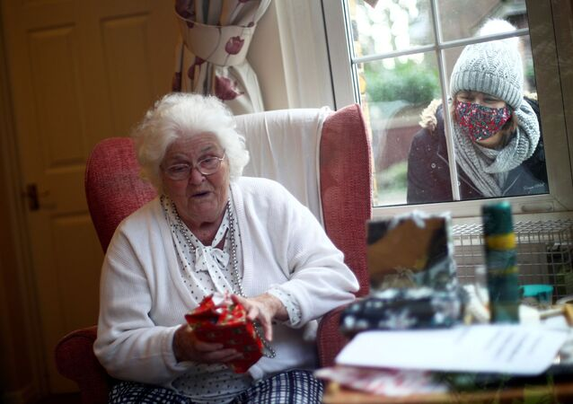 Nicky Clough looks through the window at her mother Pam Harrison opening a present on Christmas Day at Alexander House Care Home, as the spread of the coronavirus disease (COVID-19) continues, in Wimbledon, London, Britain, December 25, 2020