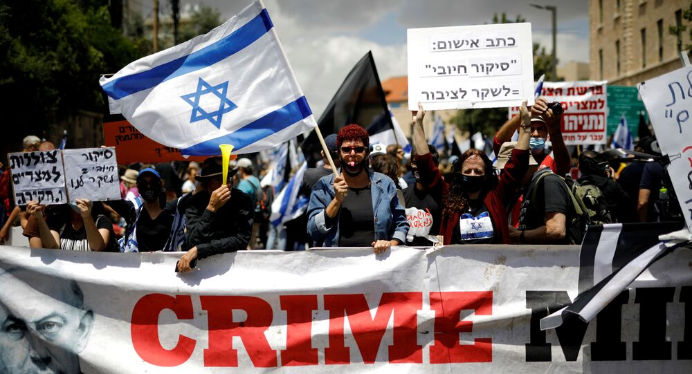 Protesters wave an Israeli flag and hold placards as they stand behind a banner reading, Crime Minister and demonstrate against Israeli Prime Minister Benjamin Netanyahu just before his corruption trial opens, outside his residence in Jerusalem May 24, 2020.