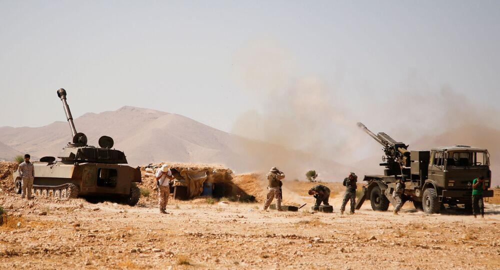 Hezbollah fighters stand near military tanks in Western Qalamoun, Syria August 23, 2017.