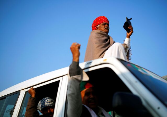 A farmer sits on a vehicle as others gesture at the site of a protest against new farm laws at a state border on a national highway in Shahjahanpur, in the desert state of Rajasthan, near New Delhi, India, December 26, 2020