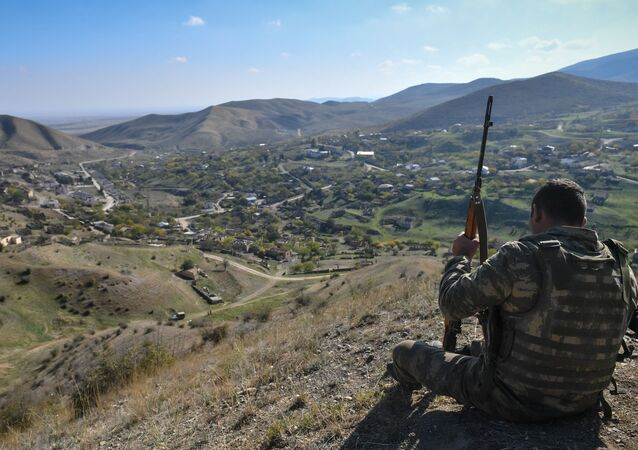 Servicemen of the Azerbaijani army during the reconstruction of hoisting the state flag at a commanding height near the village of Talish