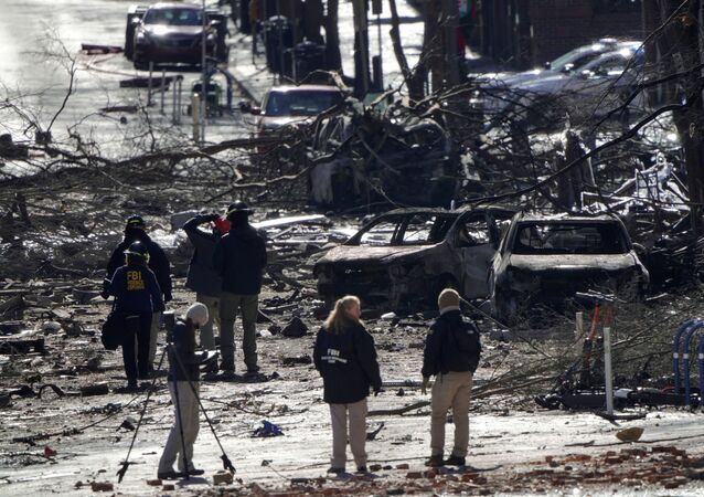 Investigators work near the blast site on 2nd Avenue in Nashville, Tennessee on 26 December after an RV exploded the day before, injuring four