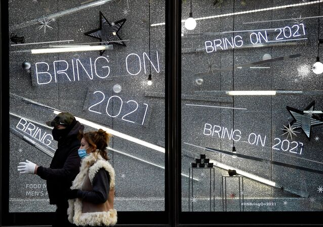 People wearing protective masks walk past a window display of a closed retail store as the British government imposes a stricter tiered set of restrictions amid the coronavirus disease (COVID-19) pandemic, in London, Britain, 20 December 2020