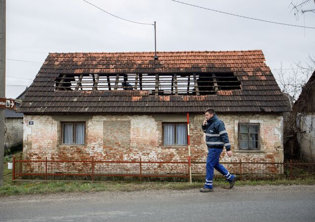A man walks next to a damaged house after a 5.2 magnitude earthquake, in Brest Pokupski village, Croatia, December 28, 2020