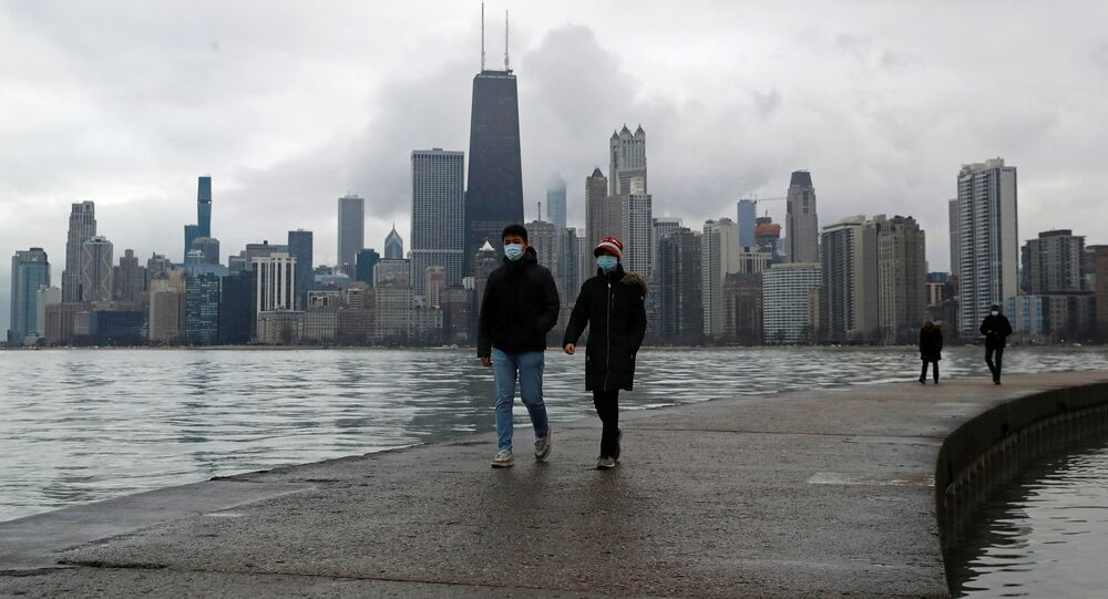 People wearing protective face masks walk, as the global outbreak of the coronavirus disease (COVID-19) continues, along the shores of Lake Michigan in Chicago, Illinois, U.S., December 6, 2020