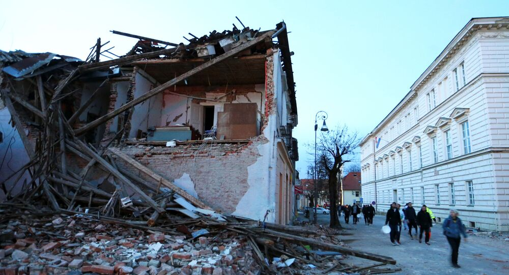 People walk past a collapsed building after an earthquake, in Petrinja, Croatia December 29, 2020.