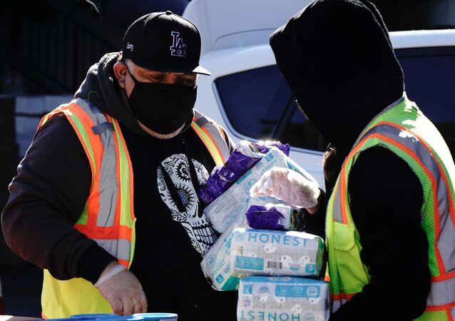 Volunteer Ismael Izzy Barrera, 45, helps load a Los Angeles Regional Food Bank patron's vehicle with food and diapers at a drive-thru food distribution, as the U.S. Senate grapples with whether to increase payments to Americans reeling from the coronavirus disease (COVID-19) pandemic, in West Covina, California, U.S. December 29, 2020.