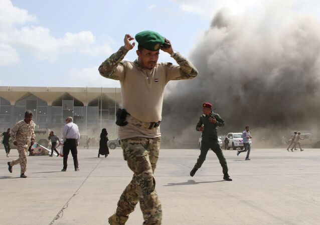 A security personnel member reacts as dust rises after explosions hit Aden airport, upon the arrival of the newly-formed Yemeni government in Aden, Yemen December 30, 2020
