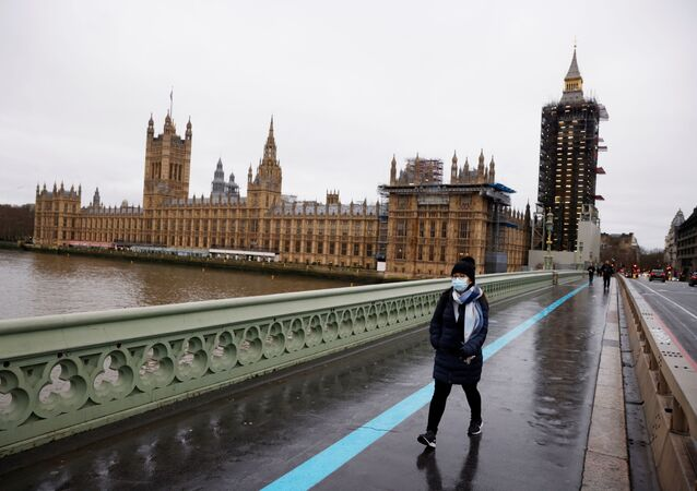 A woman wearing a face mask walks across Westminster Bridge past the Houses of Parliament, as the spread of the coronavirus disease (COVID-19) continues, in London, Britain, December 22, 2020