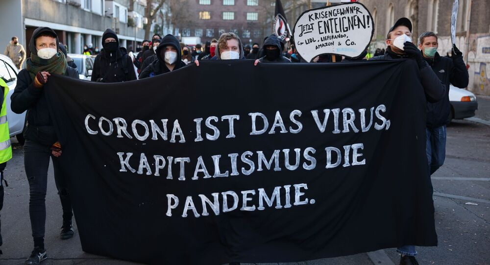 People supporting the government's restrictions hold a banner reading: Corona is the virus, capitalism is the pandemic, following the coronavirus disease (COVID-19) outbreak, in Berlin, Germany, December 30, 2020