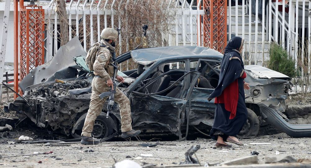 A member of Afghan security forces inspects a damaged vehicle at the site of a blast in Kabul, Afghanistan December 20, 2020.