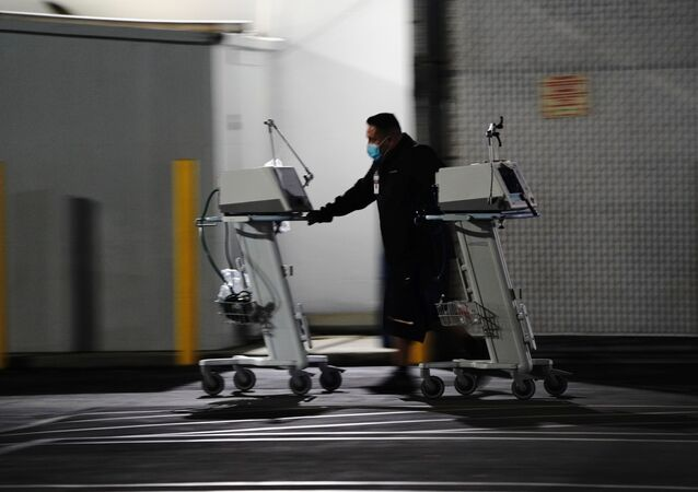 A hospital worker pushes two Computer on Wheels (COW) workstations outside the emergency room at the Community Hospital of Huntington Park during a surge in positive coronavirus cases in Huntington Park, California, U.S. December 29, 2020