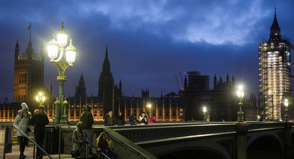 The Houses of Parliament can be seen as people walk across Westminster Bridge, during the New Year's Eve amid the coronavirus disease (COVID-19) outbreak, in London, Britain December 31, 2020