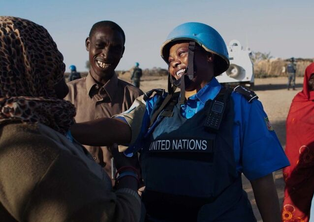 A UNAMID police officer interacts with women at a water point in Nifasha camp for internally displaced persons, north Darfur.