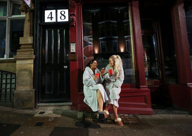 Two women celebrate New Year amid the outbreak of the coronavirus disease (COVID-19), in Newcastle, UK, 31 December 2020.