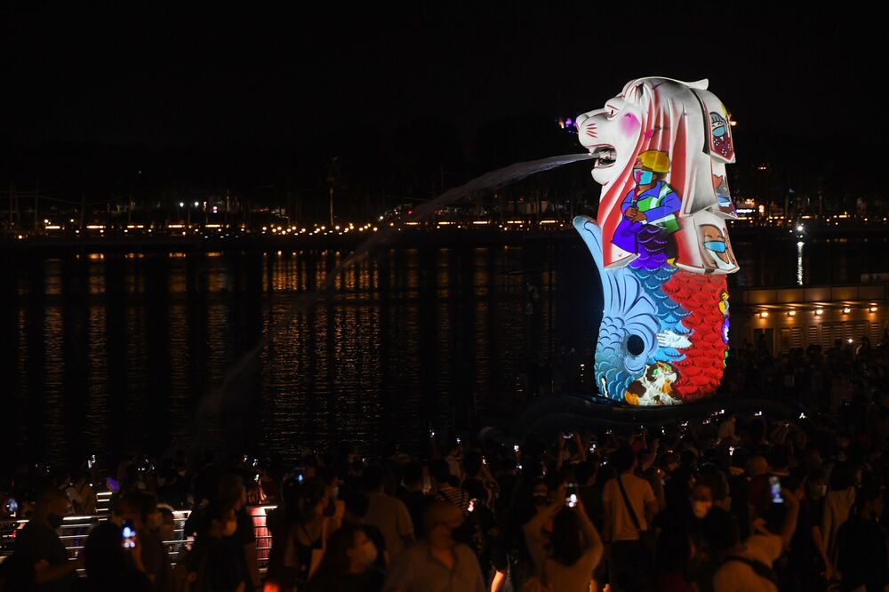 People watch as the Merlion statue is lit up as part of New Year's Eve celebrations in Singapore on 31 December 2020.