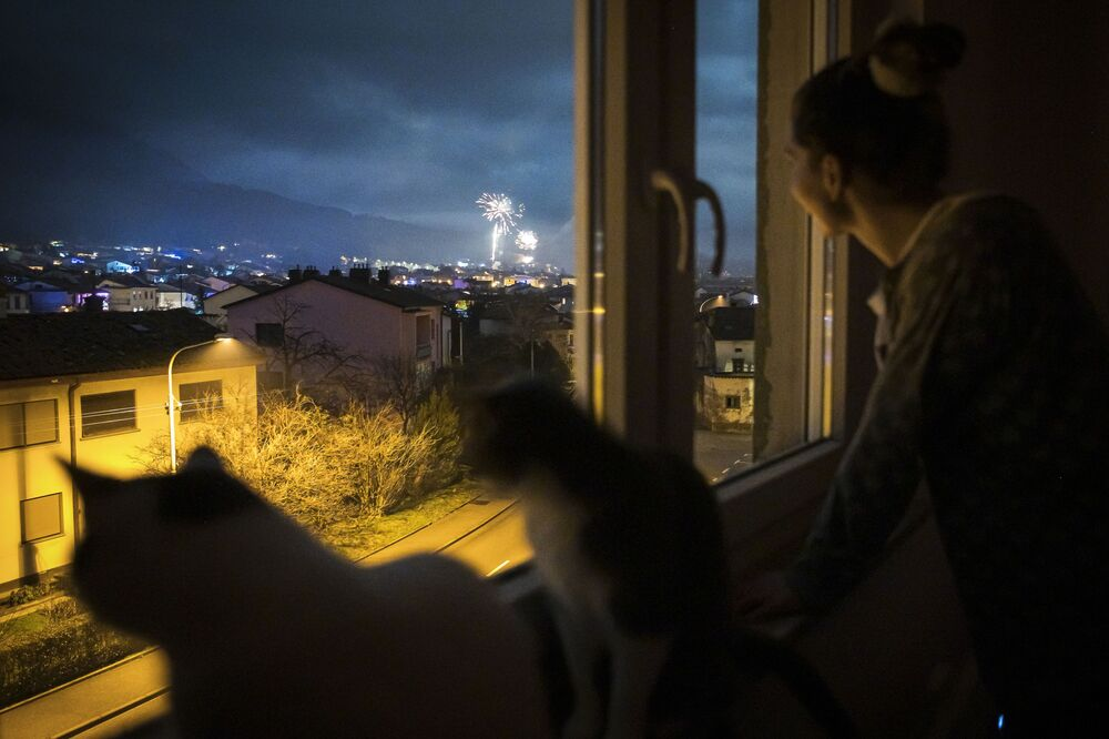 A woman and her cats look at the New Year's Eve fireworks through her window of her home in Ajdovscina, Slovenia on 1 January 2021.