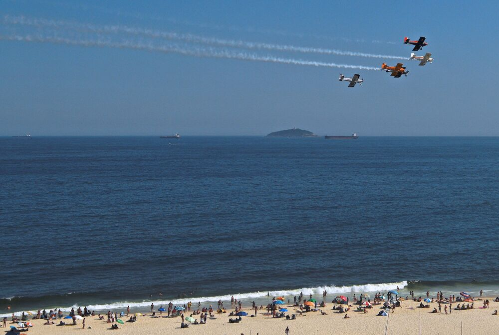 Stunt airplanes perform aerial maneuvers leaving smoke trails and entertaining beachgoers above Copacabana beach, Rio de Janeiro, Brazil, on 31 December  2020.  Rio de Janeiro's annual New Year's Eve beach bash and elaborate firework displays was cancelled due to the raging coronavirus pandemic. The city authorities will block beach access tonight, including a ban on vehicles along some 30 kilometres of Rio's coastline to prevent gatherings.