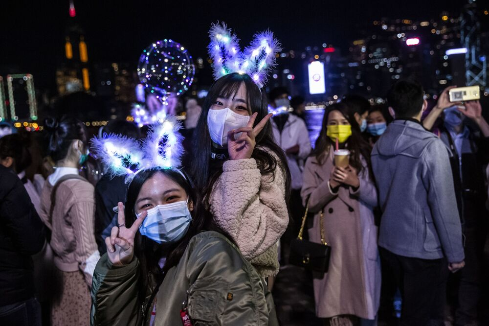 Two women gesture next to the water front of Victoria Harbour in Hong Kong on 1 January 2021, despite the COVID-19 coronavirus restrictions in place and the New Year fireworks being cancelled, people gathered to celebrate the New Year.