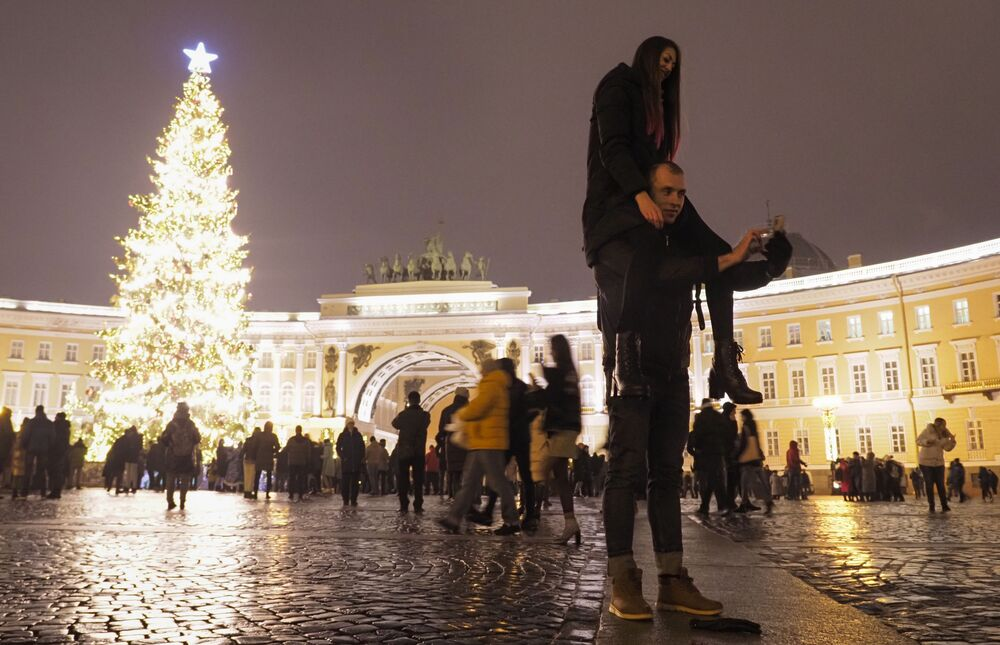 A couple take a selfie photo at the Palace Square during New Year celebration in downtown St. Petersburg, Russia, Friday 1 January 2021.