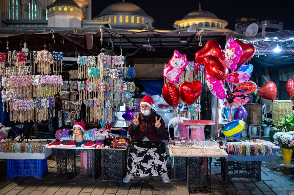 A female street vendor flashes the V for victory sign on Taksim Square in Istanbul during the New Year's celebrations in Istanbul on 31 December 2020. The Turkish government announced a four-day lockdown between 31 December and 4 January 2021.