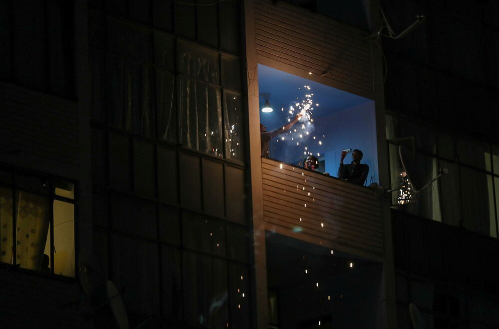Revellers celebrate at a balcony during a police patrol on New Year's Day as a nighttime curfew is reimposed amid a nationwide coronavirus disease (COVID-19) lockdown, in Johannesburg, South Africa, 1 January 2021.