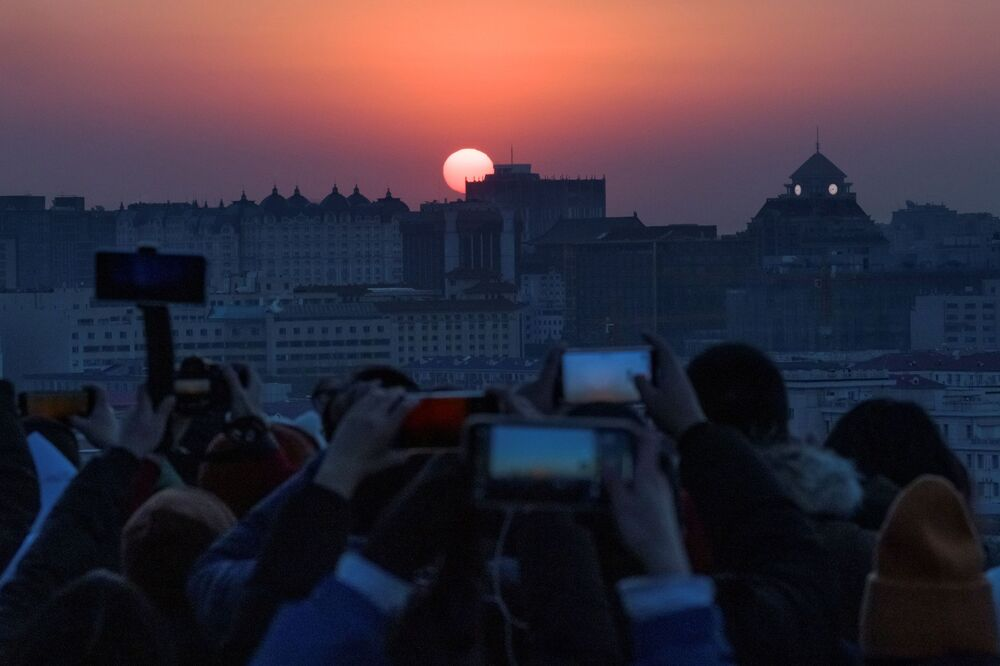 People take pictures of the first sunrise of the New Year following an outbreak of the coronavirus disease (COVID-19) in Beijing, China, 1 January 2021.