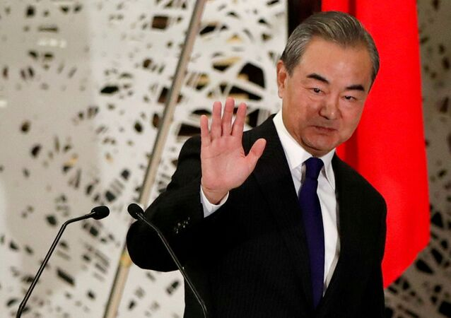 China's State Councillor and Foreign Minister Wang Yi waves as he leaves a news conference in Tokyo, Japan, November 24, 2020. REUTERS/Issei Kato/Pool/File Photo