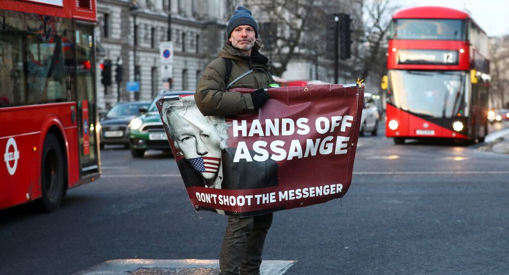 A man rides a skateboard holding a banner with an image of Julian Assange in London, Britain, December 30, 2020