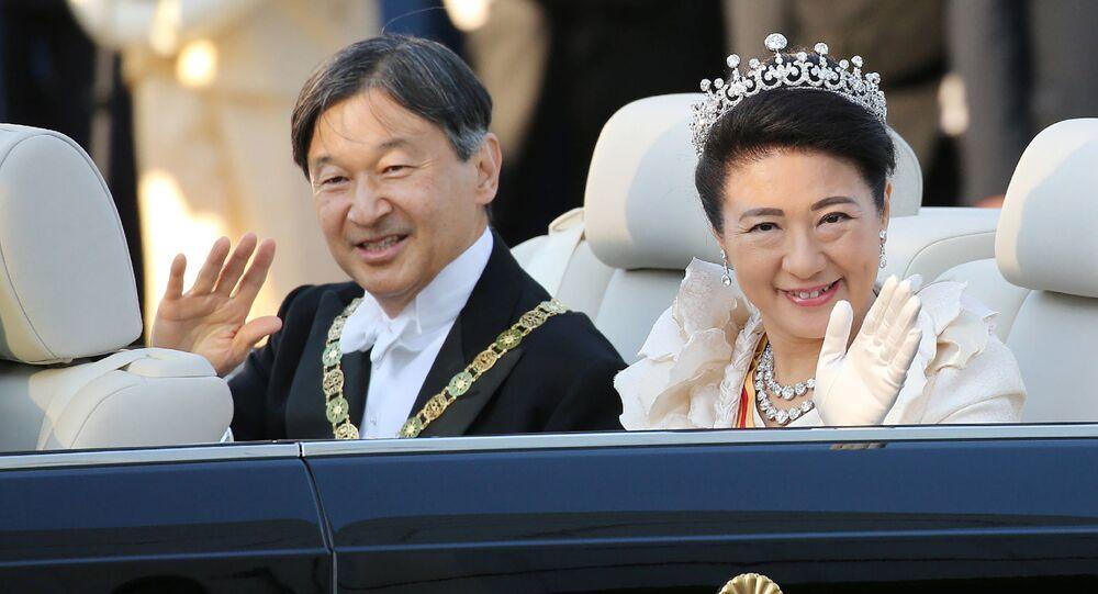 Japan's Emperor Naruhito (L) and Empress Masako (R) wave during a royal parade in Tokyo on November 10, 2019.