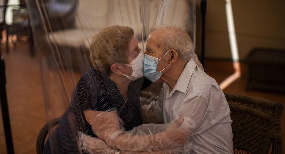 Agustina Cañamero, 81, and Pascual Pérez, 84, hug and kiss through a plastic film screen to avoid contracting the new coronavirus at a nursing home in Barcelona, Spain, Monday, June 22, 2020.