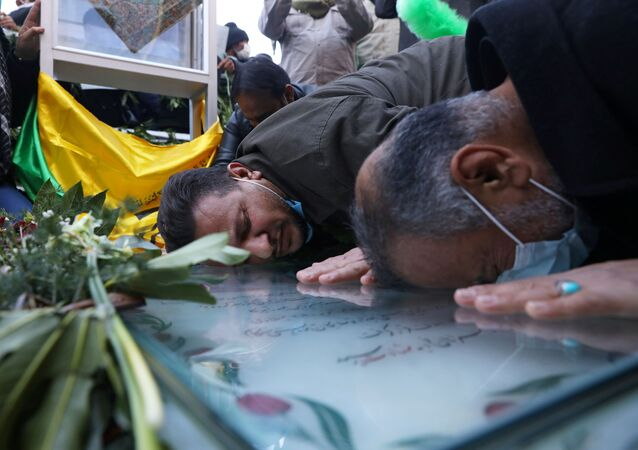 People mourn by the grave of senior Iranian military commander General Qasem Soleimani, during the one year anniversary of his killing in a US attack, in his hometown of Kerman, Iran, 2 January 2021.